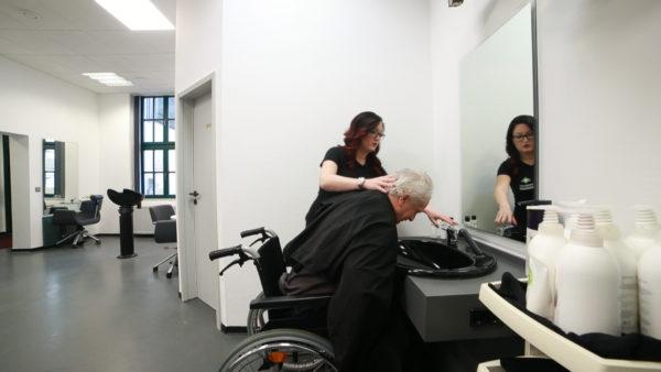 Rollstuhlfahrer beim Friseurbesuch