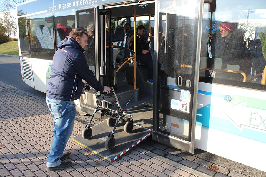 Mensch mit Gehbehinderung steigt in den Bus ein.